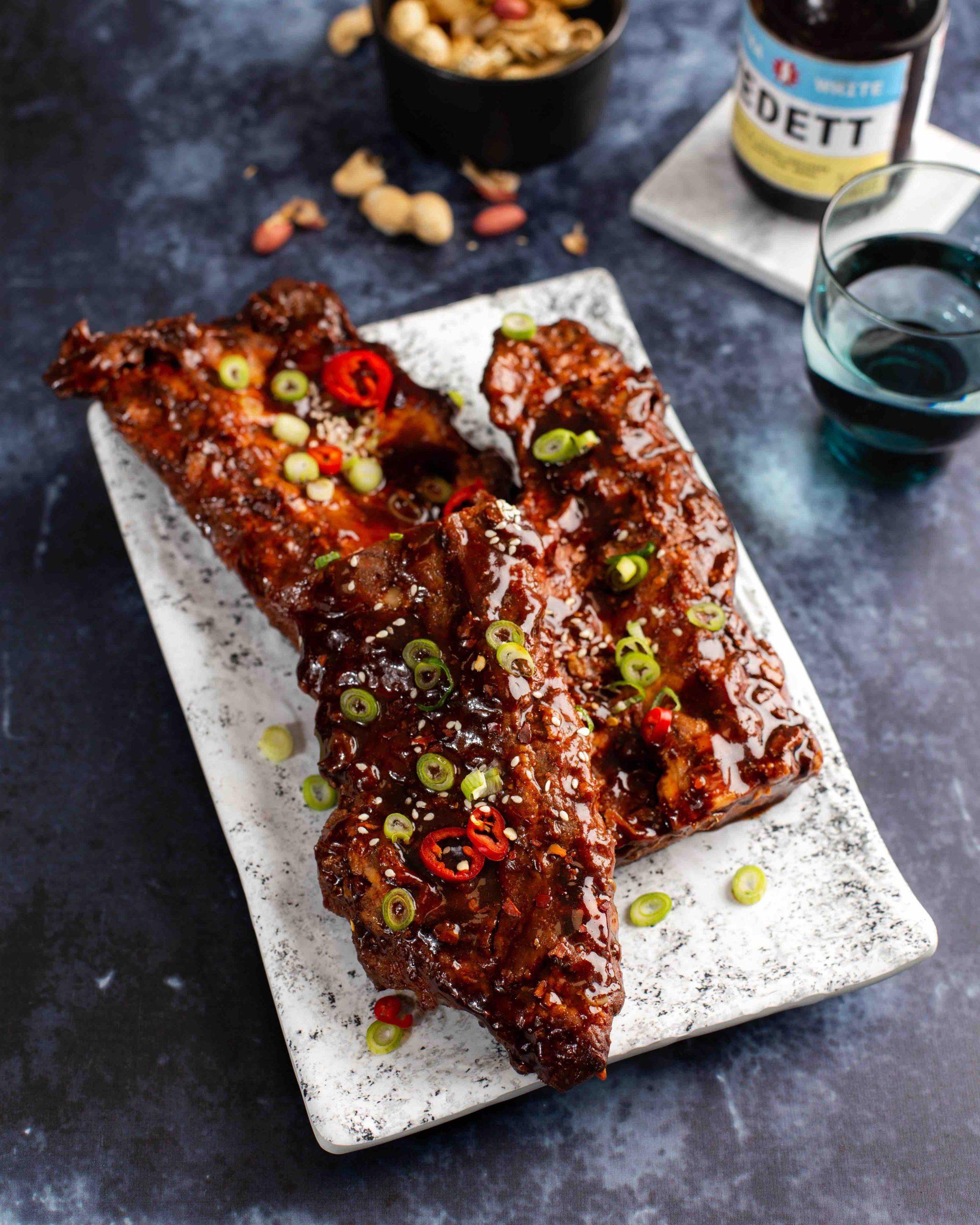 Spare ribs op bord met lente ui, sesamzaad en rode peper